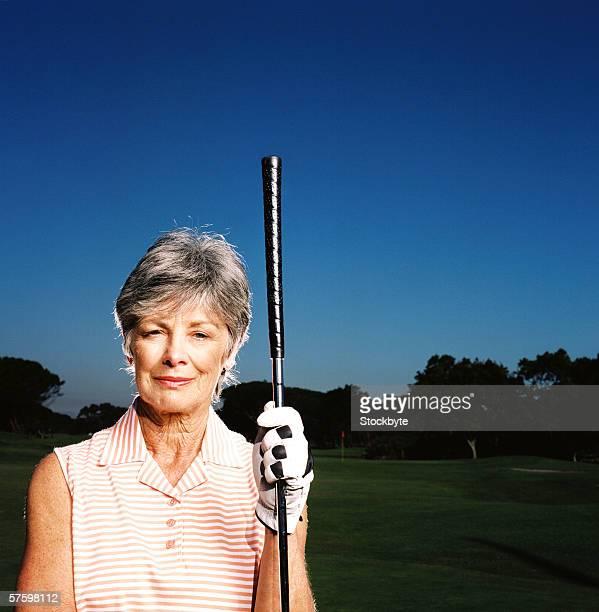 Portrait of an elderly woman holding a golf club