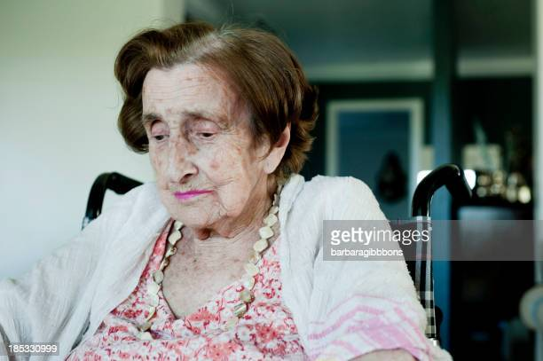 Portrait of an elderly woman in a wheelchair looking down