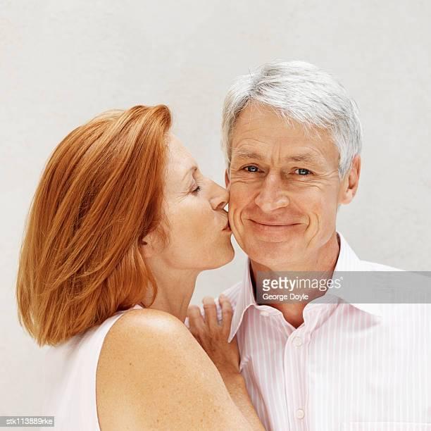 Portrait of an elderly woman kissing an elderly man on the cheek