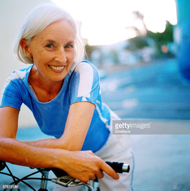 Portrait of an elderly woman smiling leaning forward on bicycle handlebars