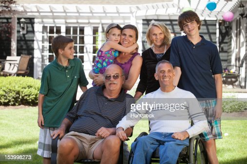 Portrait of an extended family with a man with spinal cord injury in wheelchair : Foto de stock
