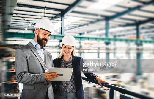 A portrait of an industrial man and woman engineer with tablet in a factory, working. : Stock Photo