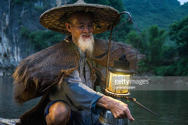 Portrait of an old chinese fisherman with lantern on bamboo boat