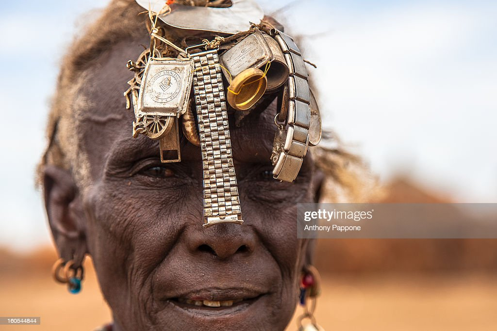 CONTENT] portrait of an old woman ethnic Dassanech with in head broken clocks to attract attention in the Omo valley, ethiopia