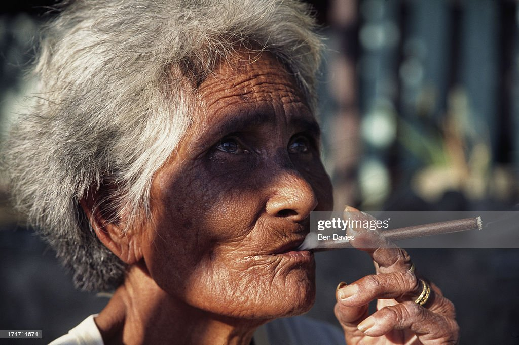 Portrait of an old woman with a wrinkled face smoking a cheroot on the island of Luzon in the Philippines Filipinos are renown worldwide for their...