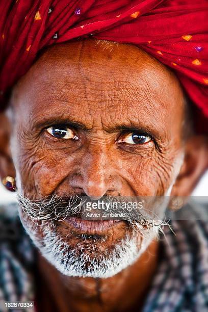 Portrait of an old worker wearing a turban and a big mustache on January 17 2012 inside a textile factory Rajasthan India