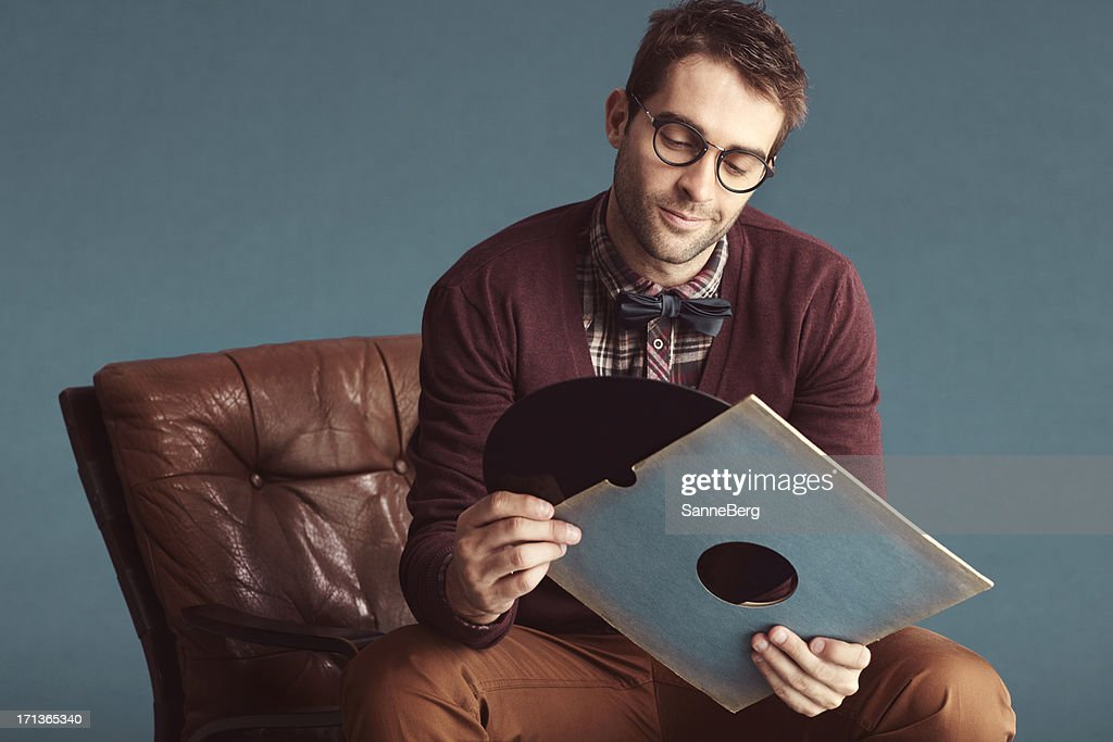 Portrait of an old-fashioned male looking at a LP
