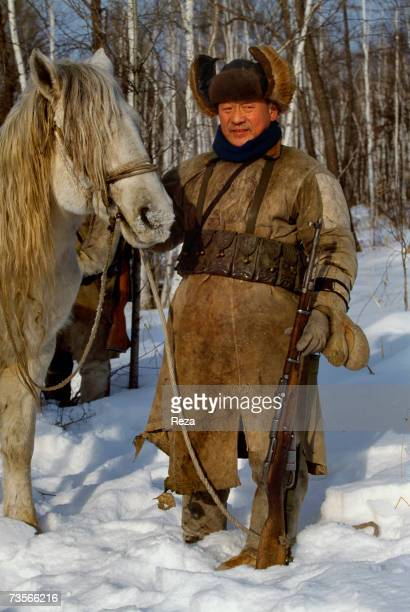 Portrait of an Oroqen hunter carrying a rifle with his horse near Xin Cheng Huo China in February 1999