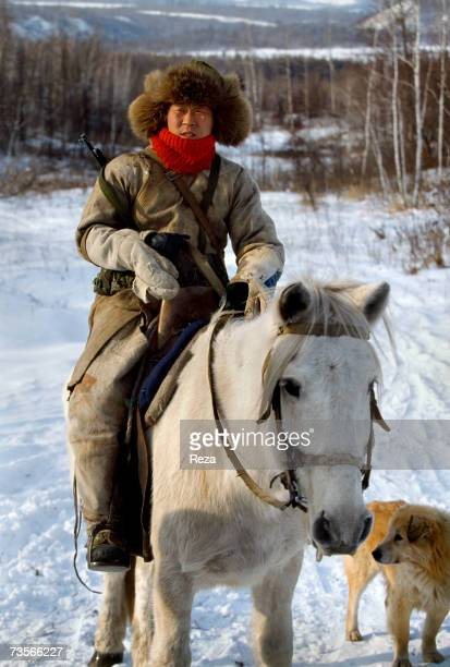 Portrait of an Oroqen hunter on his horse carrying a rifle and accompanied by a dog near Xin Cheng Huo China in February 1999
