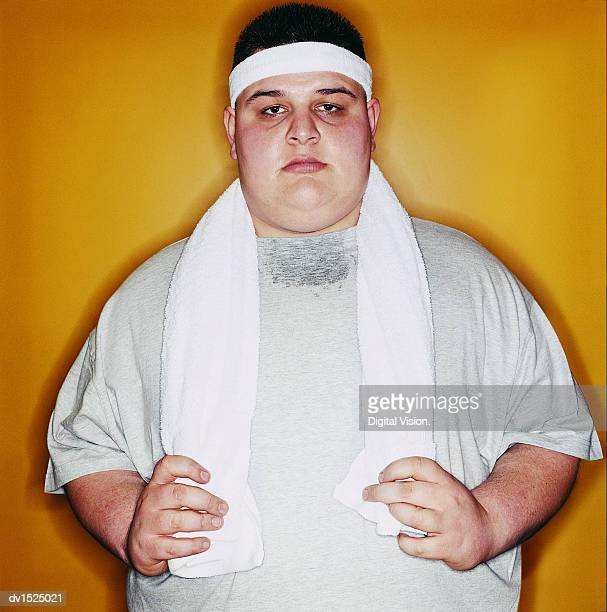 Portrait of an Overweight Young Man With a Towel and Wearing a Sweatband