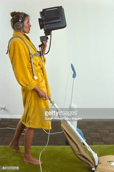 Portrait of an unidentifed model barefoot in a yellow bathrobe as she operates a vacuum cleaner and wears a video camera in a chest harness and a...
