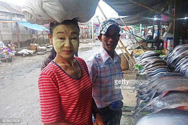 Portrait of an unidentified couple at an outdoor fish market Pyay Myanmar 2013 The woman balances a bundle on her head and wears thanaka paste on her...
