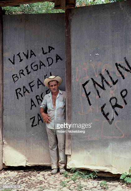 Portrait of an unidentified farmer as he stands at his door which features graffiti in support of the Popular Revolutionary Forces guerrillas San...
