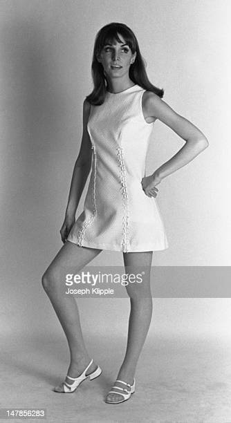 Portrait of an unidentified fashion model dressed in a white sleeveless mini dress and white sandals as she poses with one hand on her hip against a...