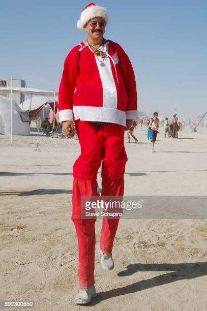 Portrait of an unidentified festival goer as he walks on stilts in a Santa Claus costume during the Burning Man Festival in the Black Rock Desert...