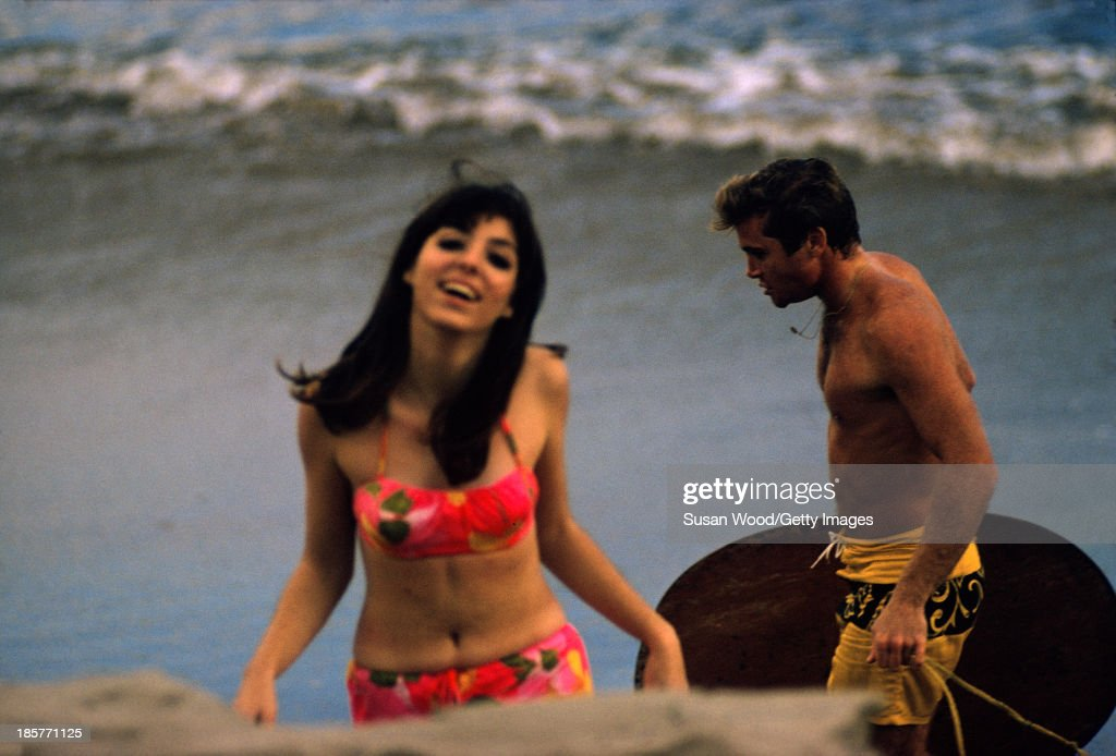 Portrait of an unidentified male and female model in swimsuits on the sand at Surfrider Beach, Malibu, California, January 1966. The photo was taken as part of a fashion shoot for Glamour Magazine.
