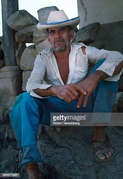 Portrait of an unidentified man as he sits on a pile of rocks in village controlled by Popular Revolutionary Forces guerrillas Corinto El Salvador...