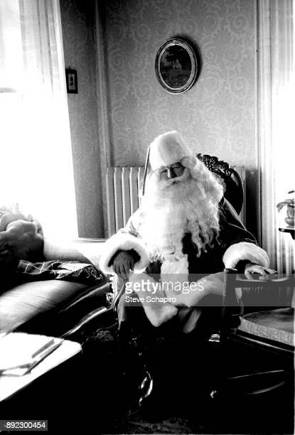 Portrait of an unidentified man in a Santa Claus costume as he sits in a living room Albion New York 1963