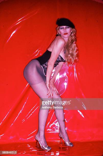 Portrait of an unidentified model dressed in a black beret bustier pantyhose and high heels as she poses against a red vinyl background New York 1980s