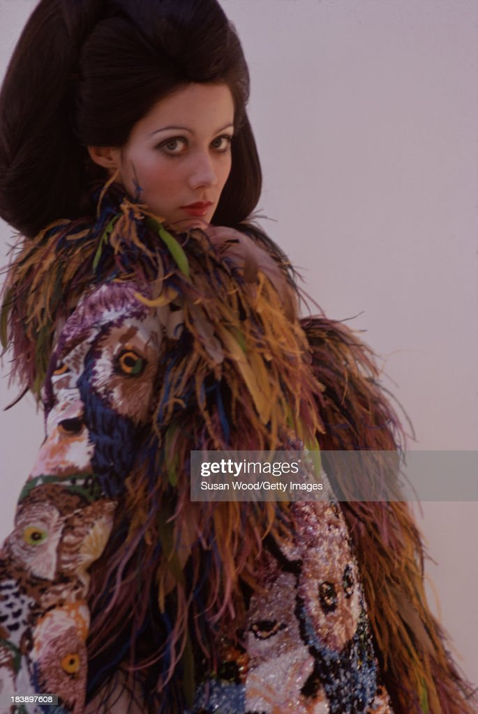 Portrait of an unidentified model dressed in a feather boa and a full-length coat, embroidered with owl heads, August 1971. The image was taken during a fashion shoot for British Vogue magazine.