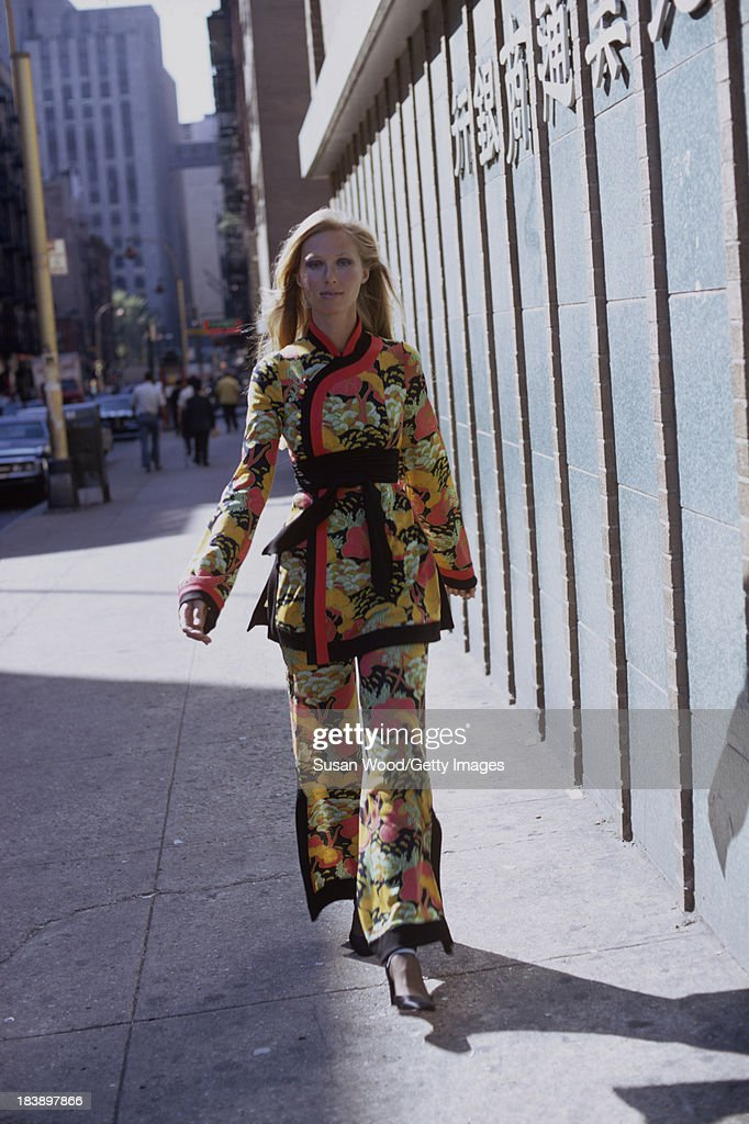 Portrait of an unidentified model dressed in a two-piece, print trouser suit as she walks on the streets of Manhattan's Chinatown, New York, New York, August 1971. The clothing, a Chinese-inspired design by John Weitz, was featured in this fashion shoot for New York magazine.
