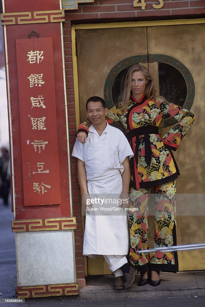 Portrait of an unidentified model dressed in a two-piece, print trouser suit as she pose with a restaurant worker in a doorway, Manhattan's Chinatown, New York, New York, August 1971. The clothing, a Chinese-inspired design by John Weitz, was featured in this fashion shoot for New York magazine.