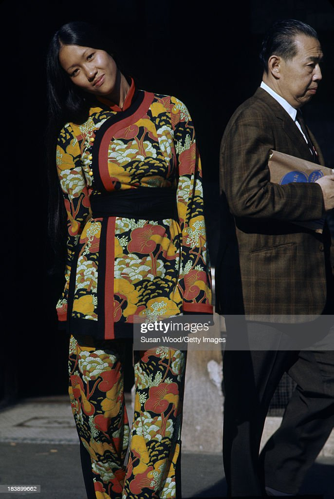 Portrait of an unidentified model dressed in a two-piece, print trouser suit as she poses on the streets of Manhattan's Chinatown, New York, New York, August 1971. A pedestrian walks behind her. The clothing, a Chinese-inspired design by John Weitz, was featured in this fashion shoot for New York magazine.