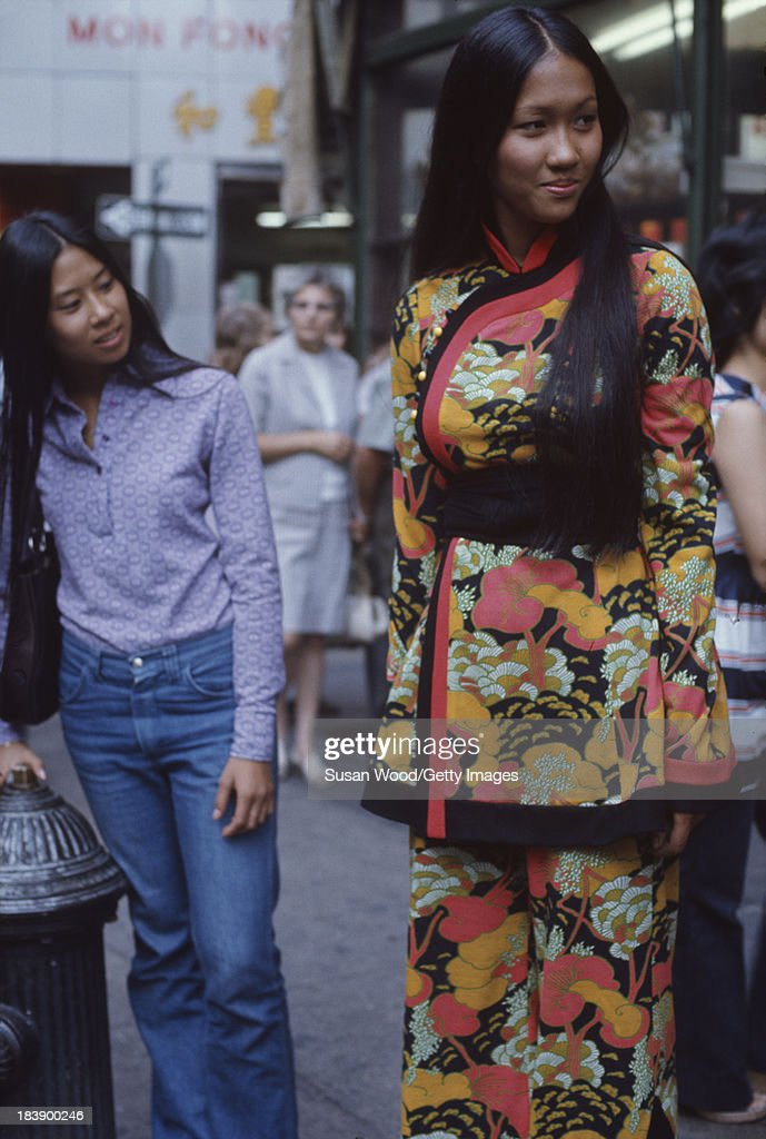 Portrait of an unidentified model dressed in a two-piece, print trouser suit as she poses on the streets of Manhattan's Chinatown, New York, New York, August 1971. A pedestrian looks at her clothes. The clothing, a Chinese-inspired design by John Weitz, was featured in this fashion shoot for New York magazine.