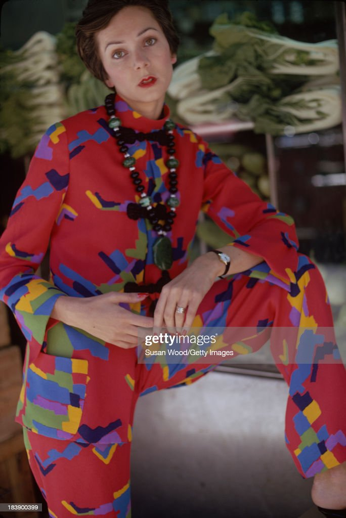 Portrait of an unidentified model dressed in a two-piece, print trouser suit and beaded cross necklace, Manhattan's Chinatown, New York, New York, August 1971. The clothing, a Chinese-inspired design by John Weitz, was featured in this fashion shoot for New York magazine.