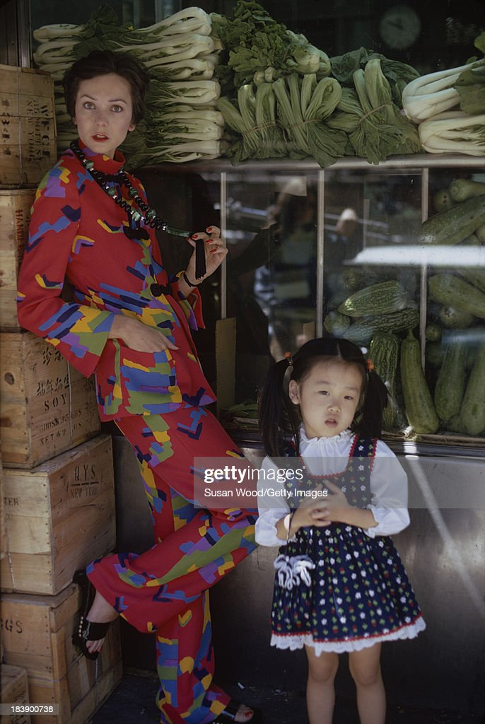 Portrait of an unidentified model dressed in a two-piece, print trouser suit and beaded cross necklace, Manhattan's Chinatown, New York, New York, August 1971. A child in a spotted pinafore and white blouse stands with her. The clothing, a Chinese-inspired design by John Weitz, was featured in this fashion shoot for New York magazine.