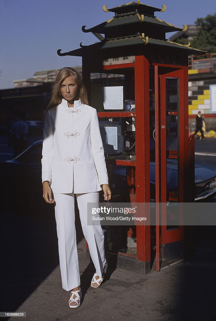 Portrait of an unidentified model dressed in a white, two-piece trouser suit as she poses beside a stylized phone booth, Manhattan's Chinatown, New York, New York, August 1971. The clothing, a Chinese-inspired design by John Weitz, was featured in this fashion shoot for New York magazine.