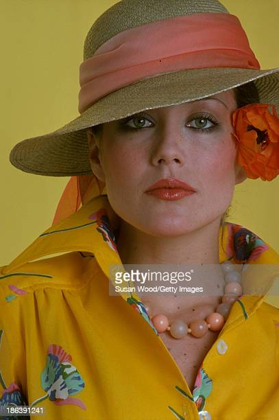 Portrait of an unidentified model dressed in a yellow print blouse bead necklace and a straw hat as she poses with a flower behind her ear against a...