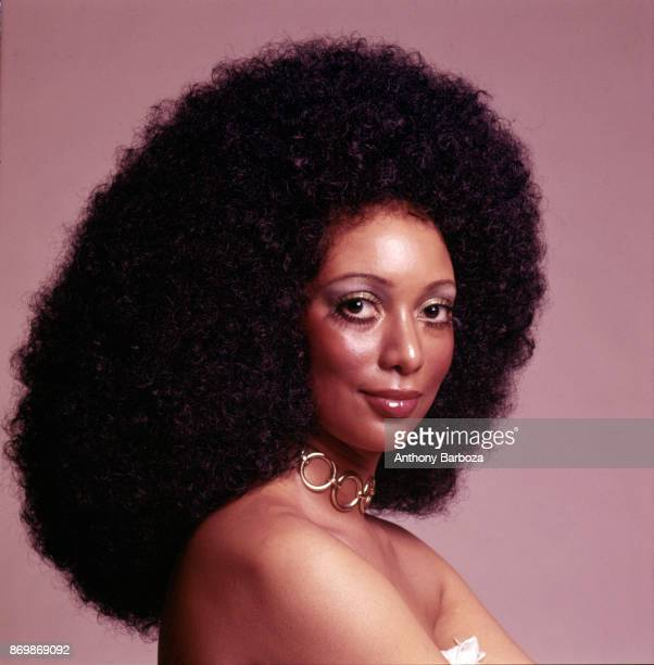 Portrait of an unidentified model her hair in an Afro and with a goldcolored ring necklace as she poses against a pink background New York 1960s