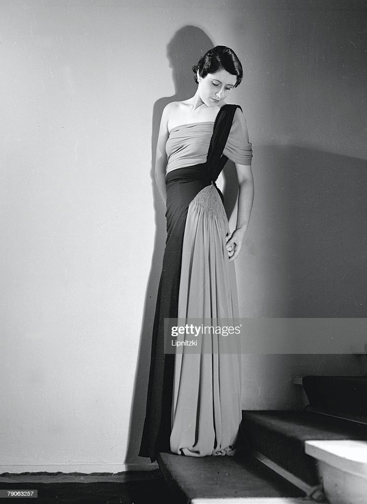 Portrait of an unidentified model in a floor-lemgth Madeleine Vionnet dress, as she stands on a staircase, September 1935.