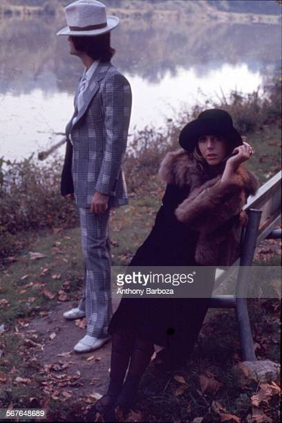 Portrait of an unidentified model in a hat and a fur stole as she sits on a bench beside the water New York 1960s Behind her is a male model in a...