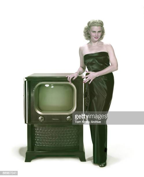 Portrait of an unidentified model in a strapless evening gown as she poses with a Motorolabrand television set in a wooden cabinet early 1950s