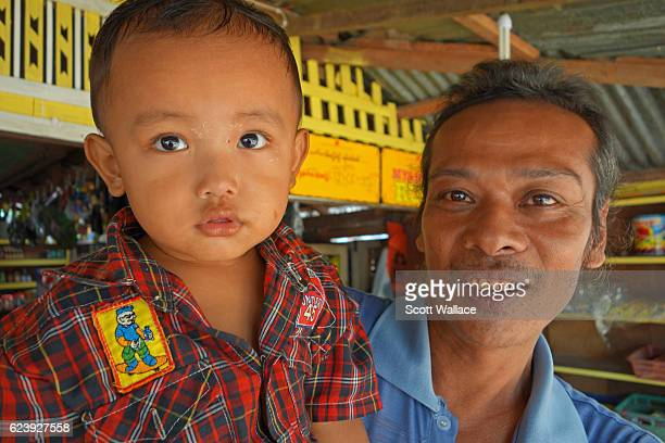 Portrait of an unidentified shopkeeper as he poses with his son at a market Tanintharyi Region Myanmar 2012 The man's teeth are stained red with...