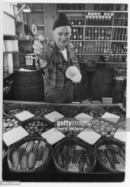 Portrait of an unidentified store clerk as he offers a pickle at Guss' Pickles New York New York February 27 1970