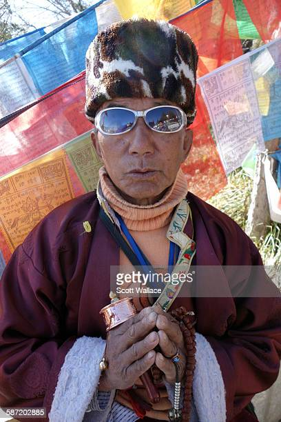 Portrait of an unidentified Tibetan Buddhist in mirrored sunglasses as he holds a prayer wheel in front of prayer flags ShangriLa Yunnan Province...