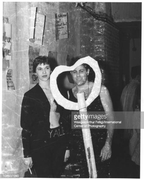 Portrait of an unidentified woman and man the latter of whom smiles as they stand behind a cutout paper heart at a party in Greenwich Village New...