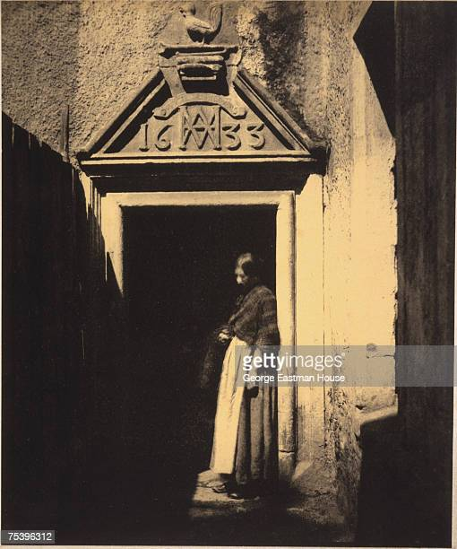 Portrait of an unidentified woman as she leans in a doorway 1850s The door features a stone header dated 1633 that features a carved rooster among...
