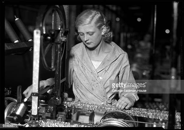 Portrait of an unidentified woman as she operates a machine with for the manufacture of the tinsel a metallic garland used in the decoration of...