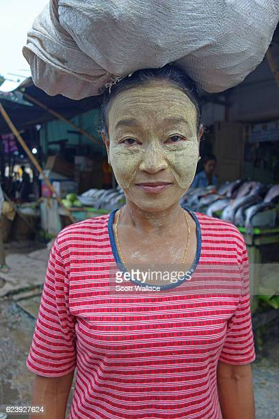 Portrait of an unidentified woman as she poses a bundle balanced on her head at an outdoor market Pyay Myanmar 2013 She wears thanaka paste on her...