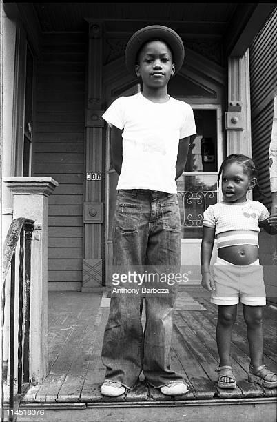 Portrait of an unidentified young boy in jeans a tshirt and hat as he stands hands behind his back with a much younger girl in shorts and a croptop...