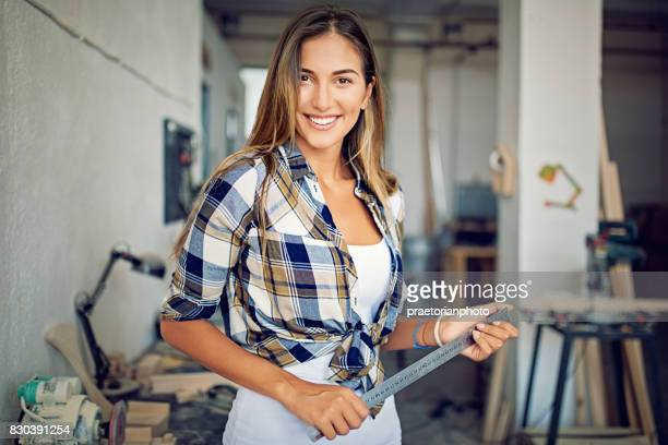 Portrait of an young girl working in a small family carpenter factory