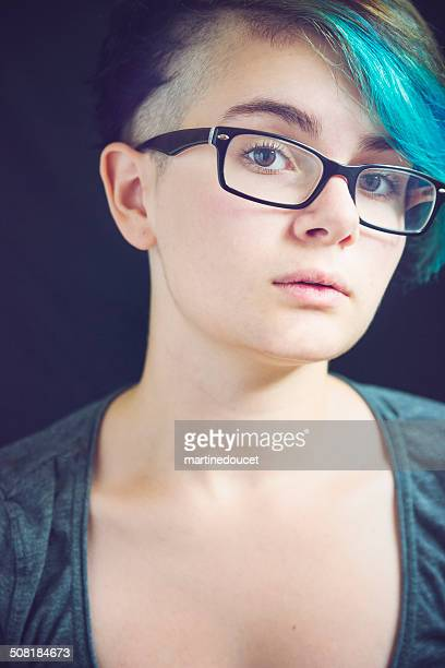 Portrait of androgynous young woman with blue hair and glasses.