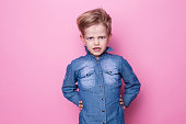 Portrait of angry beautiful little boy. Studio portrait over pink background
