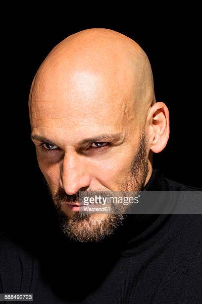 Portrait of angry man wearing black turtleneck in front of black background