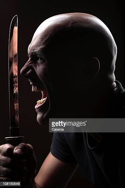 Portrait of Angry Young Man Holding Large Knife, Low Key