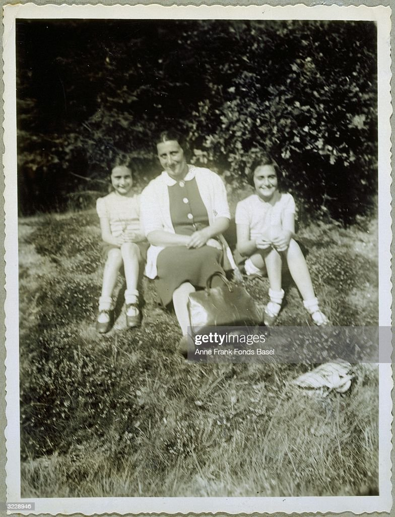 A portrait of <a gi-track='captionPersonalityLinkClicked' href=/galleries/search?phrase=Anne+Frank&family=editorial&specificpeople=173492 ng-click='$event.stopPropagation()'>Anne Frank</a> (1929 - 1945), (left) sitting with her mother, Edith, and her sister, Margot, in the grass near Villa Laret (owned by Olga Spitzer), Sils-Maria, Switzerland. From <a gi-track='captionPersonalityLinkClicked' href=/galleries/search?phrase=Anne+Frank&family=editorial&specificpeople=173492 ng-click='$event.stopPropagation()'>Anne Frank</a>'s photo album.